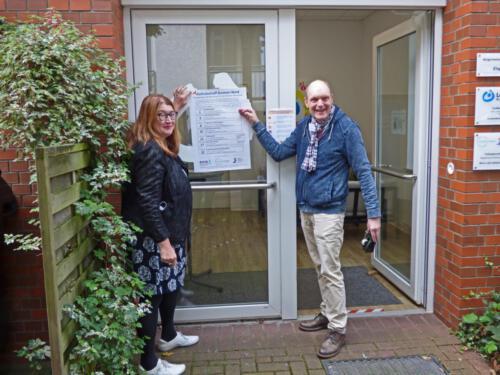 Senatorin Anja Stahmann und Gerald Wagner hängen Plakat auf